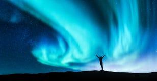 La aurora boreal y la silueta de una mujer con aumentado para arriba arma fotos de archivo libres de regalías