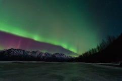 Aurora verde sobre montañas y un lago congelado Imagen de archivo