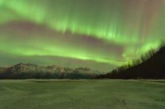 Aurora verde sobre montañas y un lago congelado Imagenes de archivo