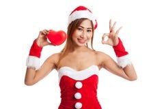La AUTORIZACIÓN asiática de la demostración de la muchacha de la Navidad con Santa Claus viste con h rojo Fotografía de archivo libre de regalías