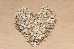 La avena forma escamas cereal en forma de corazón en superficie de madera Foto de archivo
