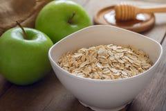 La avena forma escamas en el cuenco blanco con la manzana y la miel verdes frescas Foto de archivo libre de regalías