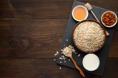 La avena forma escamas en el cuenco y la miel, las pasas, leche en tablero de la pizarra y fondo de madera rústico Foto de archivo