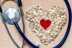 La avena forma escamas en forma de corazón y estetoscopio Fotografía de archivo