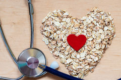 La avena forma escamas en forma de corazón y estetoscopio Fotos de archivo