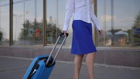 La azafata del retrato en uniforme va y guarda la maleta en aeropuerto del fondo almacen de video