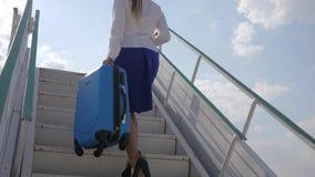 La azafata en aeropuerto se sostiene en maleta y pasaporte de las manos con el billete de avión almacen de video