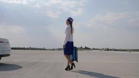 La azafata en los tacones altos y el uniforme con la maleta corre a lo largo de aeropuerto almacen de video