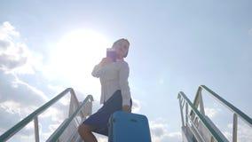 La azafata en soportes del uniforme en las escaleras del avión sostiene la maleta y el pasaporte con el billete de avión almacen de video