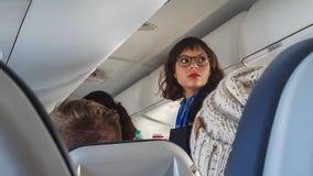 La azafata en vidrios mira hacia la parte posterior del avión vista sobre las cabezas de pasajeros que se sientan imágenes de archivo libres de regalías