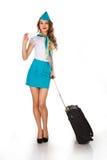 La azafata hermosa sostiene equipaje y una tarjeta Fotos de archivo libres de regalías