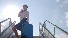 La azafata sostiene la maleta y el pasaporte de las manos en las escaleras del avión en aeropuerto en contraluz almacen de video