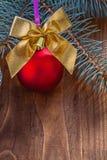 La babiole rouge et l'or de Noël colorés cintrent avec la petite cloche sur vieux Photos stock