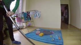 La babysitter si occupa della figlia del bambino e pulisce a casa con l'aspirapolvere 4K archivi video