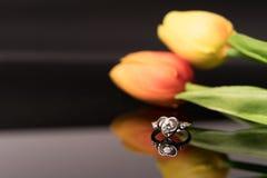 La bague à diamant avec des tulipes fleurissent les milieux, anneaux de luxe avec l'espace de copie Image stock