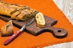 La baguette avec la graine de lin a coupé sur le panneau de cuisine Photographie stock libre de droits