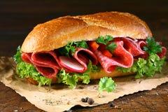 Baguette avec de la laitue et le salami frais Photographie stock
