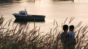 La bahía hermosa con un powerboat en la puesta del sol, el padre detiene a su hijo en sus brazos le muestra el puerto y lo besa metrajes