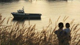 La bahía hermosa con un powerboat en la puesta del sol, el padre detiene a su hijo en sus brazos le muestra el puerto y lo besa almacen de metraje de vídeo