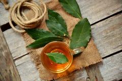 La bahía orgánica deja té en una tabla de madera del vintage Foto de archivo libre de regalías