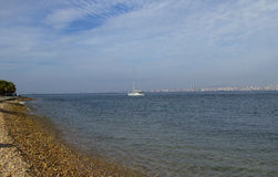 La baia del mare con le pietre tira e mare, singolo yacht immagini stock