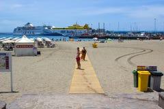 La baia a ed il terminale di traghetto sabbiosi a Los Cristianos in Tenerife con l'isola ferries nei creatori di festa e del port Fotografia Stock