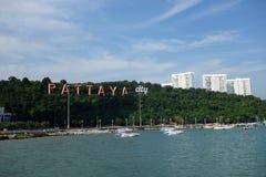 La baie de Pattaya avec les bateaux commerical et la ville de Pattaya signent Photo stock