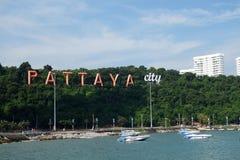 La baie de Pattaya avec les bateaux commerical et la ville de Pattaya signent Images stock