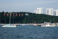 La baie de Pattaya avec les bateaux commerical et la ville de Pattaya signent Photographie stock libre de droits