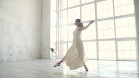 La bailarina baila en un vestido de la luz blanca bailarín de ballet en zapatos del pointe Facilidad y tolerancia Cámara lenta metrajes