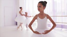 La bailarina de la muchacha se coloca en actitud del ballet Profesor con la muchacha en fondo metrajes