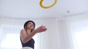 La bailarina de la mujer joven lanza para arriba objetos de un círculo metrajes