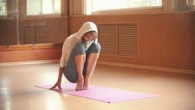 La bailarina de la mujer joven se coloca en sus dedos del pie de la extremidad en la estera de la yoga - estudio de la danza metrajes