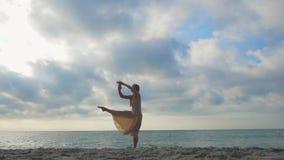 La bailarina de salto en vestido de seda beige y el punto en la arena varan cerca del mar en la salida del sol o la puesta del so almacen de video