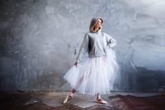 La bailarina delgada estupenda en un vestido negro está presentando en el estudio Fotos de archivo libres de regalías