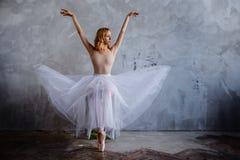 La bailarina delgada estupenda en un vestido negro está presentando en el estudio Imagen de archivo