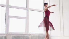 La bailarina descalza está girando en un pasillo, trasladándose a una cámara almacen de metraje de vídeo