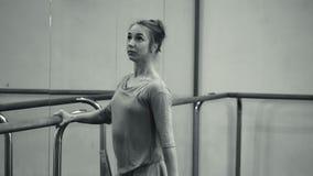 La bailarina en sweatsuit y pointe beige estira en la barra en gimnasio del ballet Mujer que coloca la barra cercana y el espejo, almacen de metraje de vídeo
