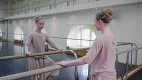La bailarina en sweatsuit y pointe beige estira en la barra en gimnasio del ballet Mujer que coloca la barra cercana y el espejo, almacen de video