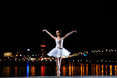 La bailarina en un vestido blanco contra de la ciudad y el riv de la noche Fotografía de archivo