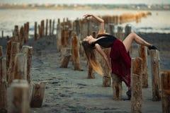 La bailarina en vestido largo está bailando en fondo de la playa Imagenes de archivo