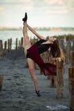 La bailarina en vestido largo está bailando en fondo de la playa Foto de archivo libre de regalías