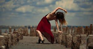La bailarina en vestido largo está bailando en fondo de la playa y del cielo Fotos de archivo