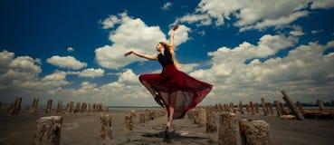 La bailarina en vestido transparente está bailando en arena en la playa y p Fotos de archivo libres de regalías