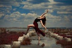 La bailarina está bailando en arena en fondo de la playa y del cielo Fotos de archivo libres de regalías