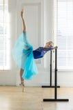 La bailarina está entrenando en la barra fotos de archivo