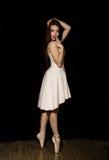 La bailarina joven con un cuerpo perfecto está bailando en zapatos del pointe en fondo oscuro Fotografía de archivo libre de regalías