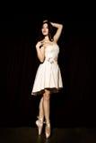 La bailarina joven con un cuerpo perfecto está bailando en zapatos del pointe en un fondo oscuro Fotos de archivo