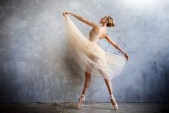 La bailarina joven en un traje de baile coloreado de oro está presentando en un estudio del desván Foto de archivo