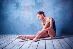 La bailarina joven que se sienta en el piso de madera Foto de archivo libre de regalías